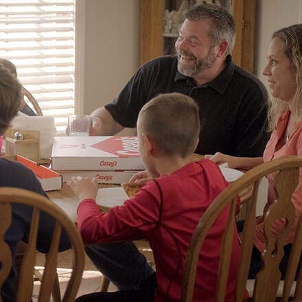 family eating pizza around a table